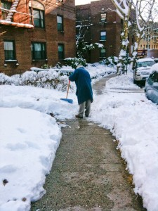 old man shovelling snow in residential Queens